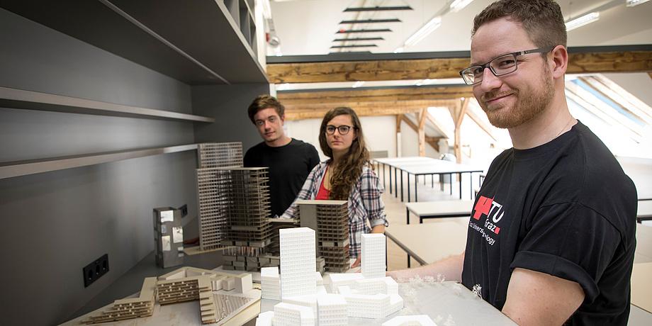 Zwei Studenten und eine Studentin zeigen stolz Architekturmodellen in den Architekturstudios der TU Graz.