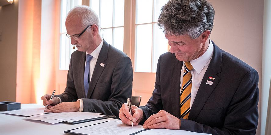 Zwei grauhaarige Männer in Anzug und Krawatte unterzeichnen zwei Dokumente.