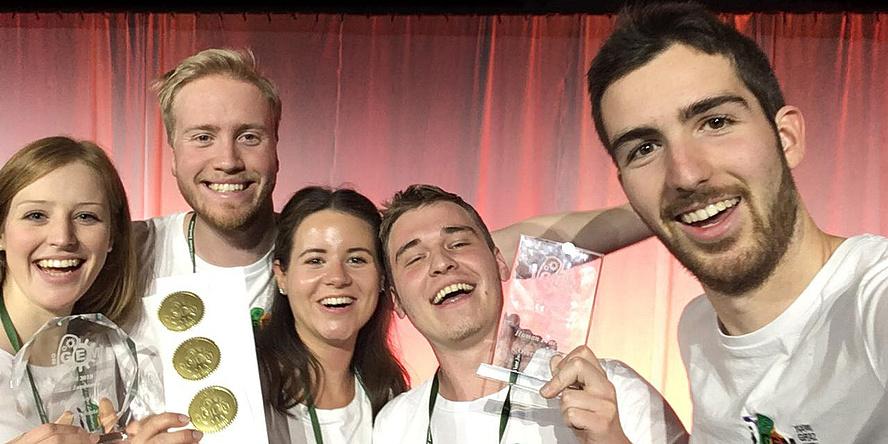 Vier jungen Menschen mit Medaillen und Urkunden