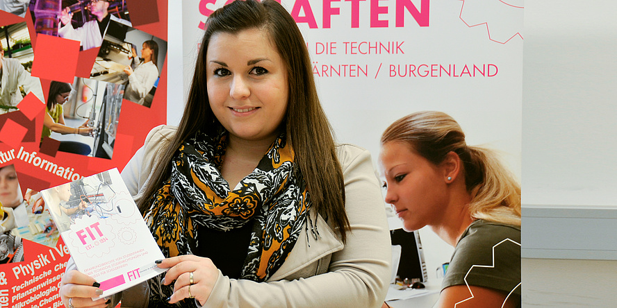 "Hillary Chrys Moisa, Bachelors student in Software development and Business Management at TU Graz, standing in front of ""Women in technology""-Posters."