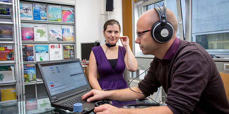 A woman and a man are sitting next to a glass table. She is wearing a necklace with a black sensor and a microphone. He is wearing headphones and using a laptop.