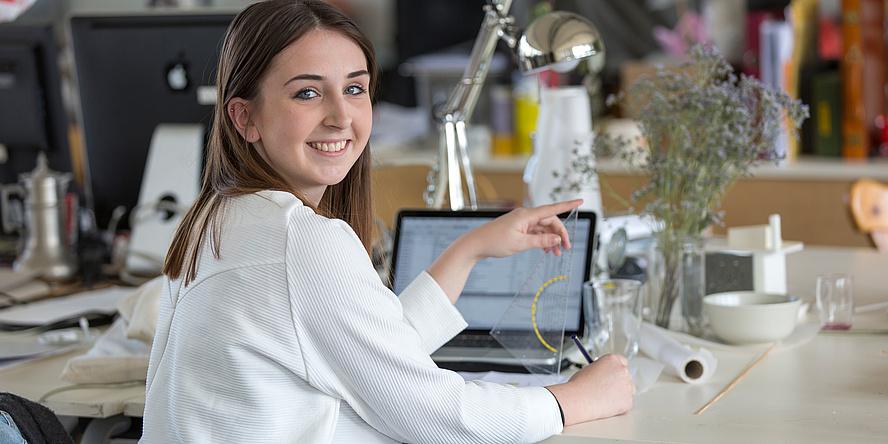 Eine Studierende der TU Graz arbeitet gut gelaunt am Laptop.