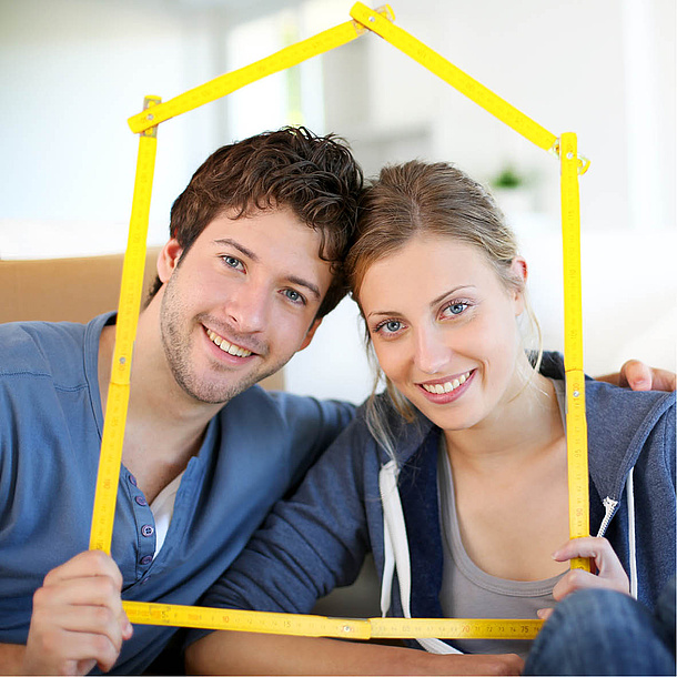 Man and woman holding folding ruler with the shape of a house. Photo source: goodluz - fotolia.com