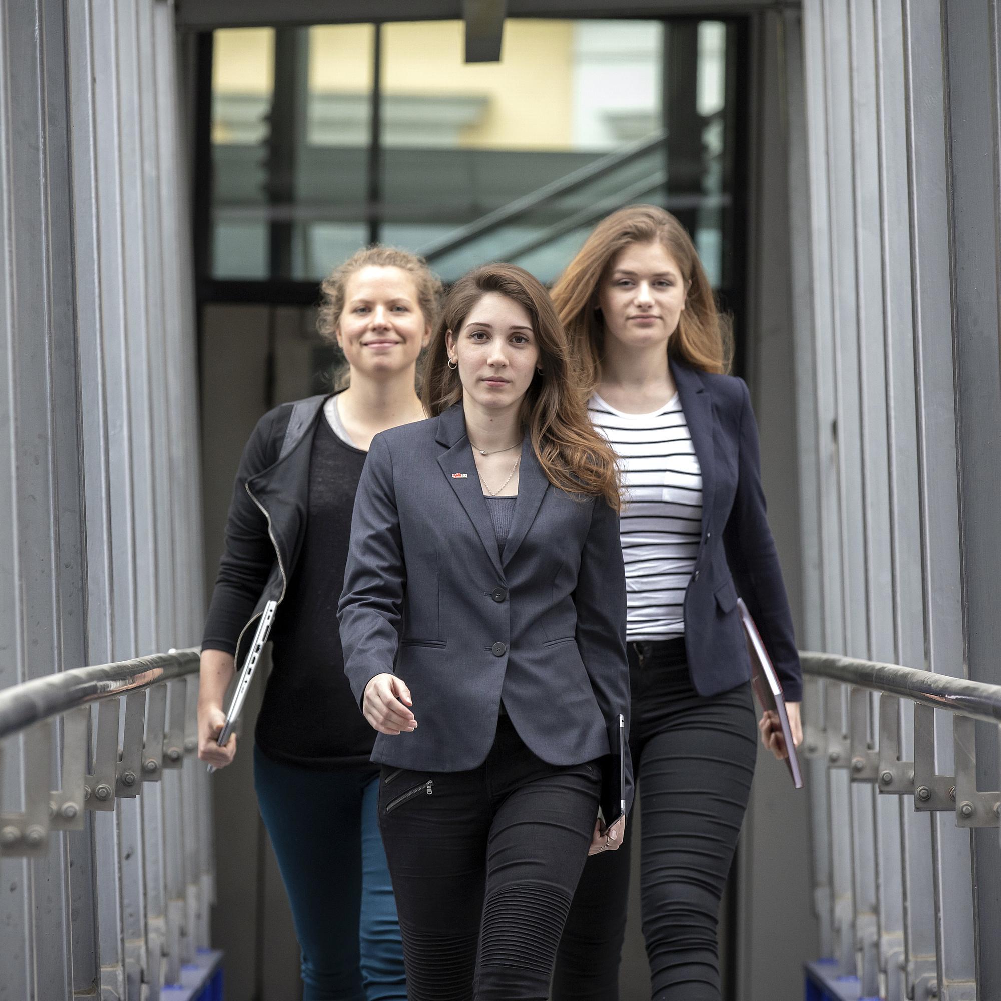 Drei junge Frauen mit entschlossenem Blick.