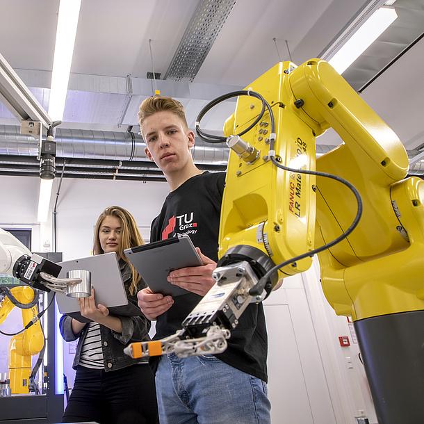 Zwei Studierende stehen mit Laptops hinter einem Roboterarm.