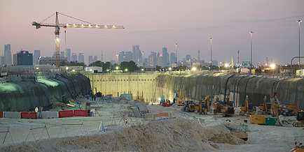 Im Vordergrund steht eine breite, tiefe Baugrube mit zig Baufahrzeugen. Seitlich steht ein Kran, dahinter sieht man die Skyline einer Großstadt.