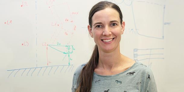 Frau vor einer Tafel mit Formeln