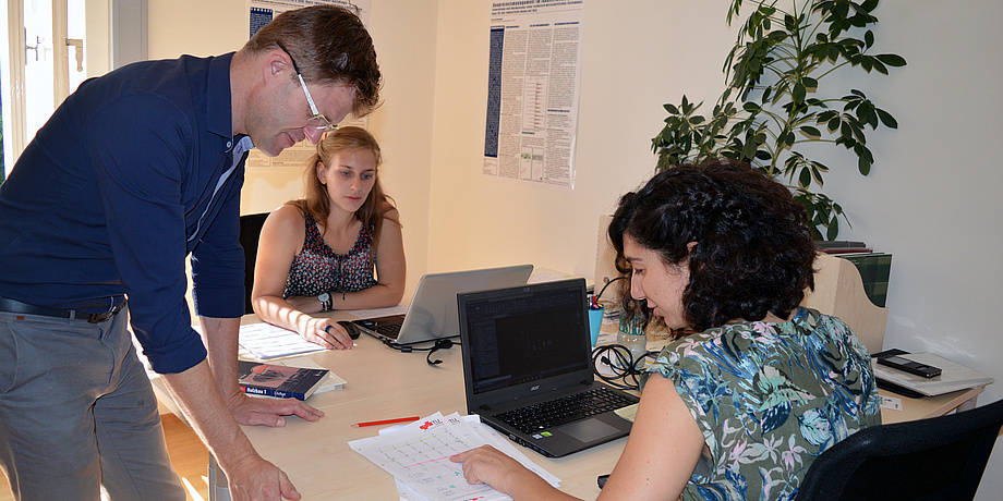 Two woman are working at a desk. A man stands besides them.