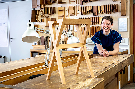 Architekturstudentin mit Hocker in Holzwerkstatt
