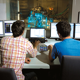 Two men in front of several screens, a machine processing behind a glass partition. Photo source: Bergmann - TU Graz