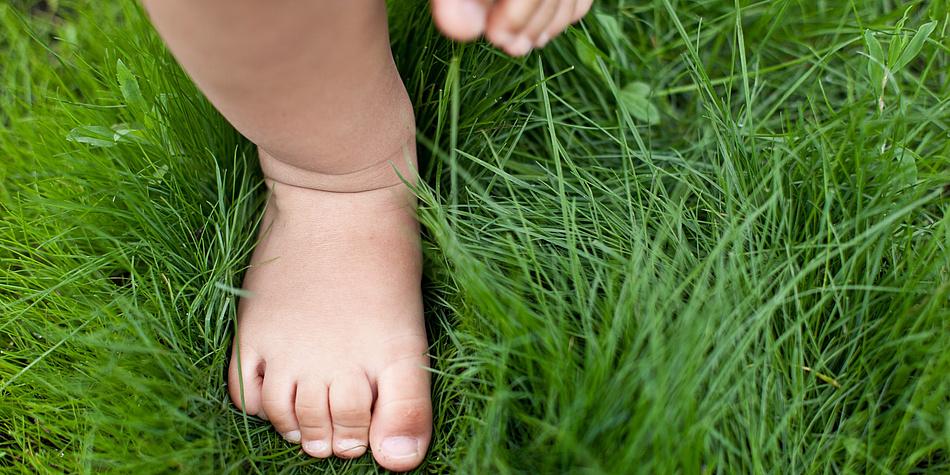 Zwei Kleinkinderfüße im grünen Gras.
