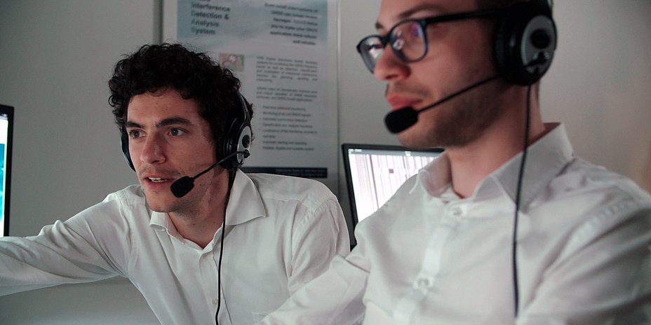 Two men with headsets in front of a screen at work.