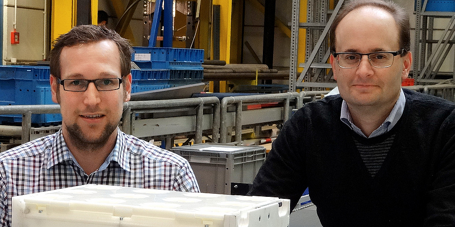 TU Graz-Forscher Florian Ehrentraut und Christian Landschützer (mit schwarzem Pulli über kleiner kariertem Hemd) zeigen in einem Labor des Institutes für Technische Logistik stolz den weißen Prototypen einer modularen Transportbox aus dem Forschungspr