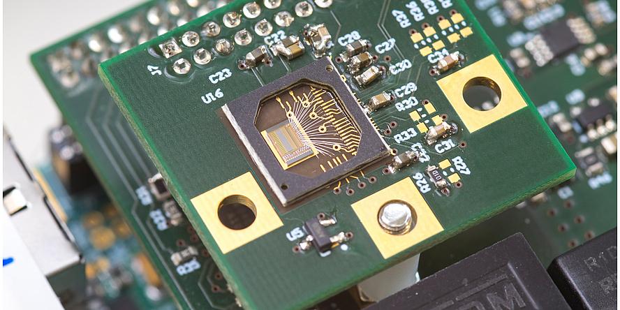 Eine grüne Platte mit mehreren goldenen Plättchen. In der Mitte ein Sensor.