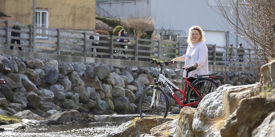 Aglaee Degros steht neben einem Bachbett und hält ein Rad im TU Graz-Design.