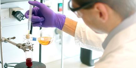 Forscher mit Spritze und Flaschkolben