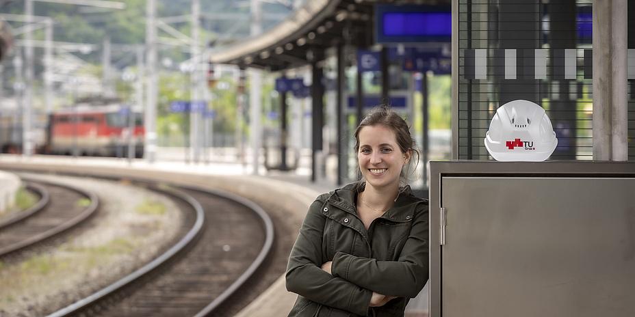 Lächelnde Frau neben Zuggleisen auf einem Bahnsteig