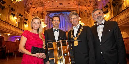 Eine Gruppe von drei Männern und einer Frau in festlicher Abendkleidung in einem Ballsaal