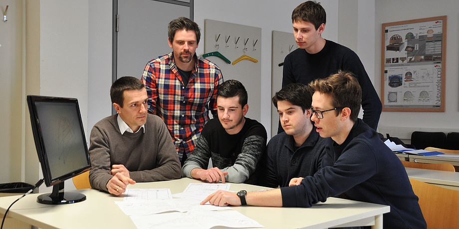 Four students and two supervisors work in front of a computer on a white table with work documents on the project for the steel bridge competition.