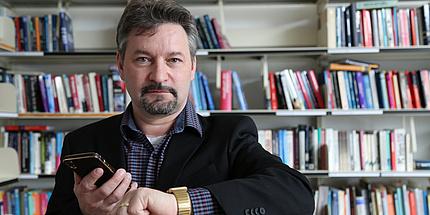 Ein Mann steht vor einem Bücherregal. Er hat beide Hände auf Brusthöhe gehoben. In der einen Hand hält er ein Smartphone, auf der anderen trägt er eine Smartwatch.