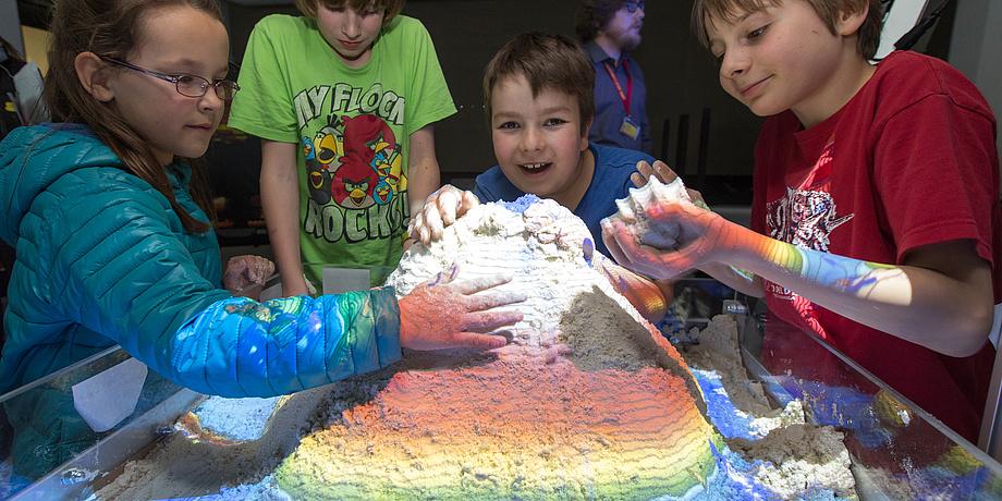 Vier Kinder spielen mit einem bunt beleuchteten Sandhaufen.