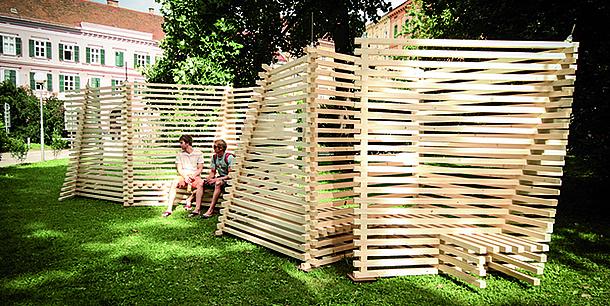 Zwei Männer sitzen auf einer modernen Parkbank aus Holz. Bildquelle: TU Graz/ITE
