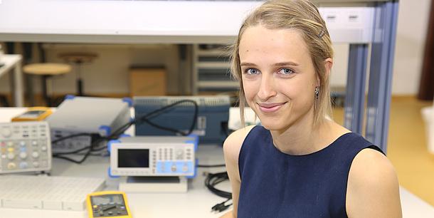Junge Frau vor einem Tisch mit elektronischen Geräten.