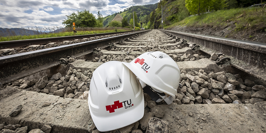 Zwischen zwei Schienen liegen zwei Helme mit dem TU Graz-Logo.