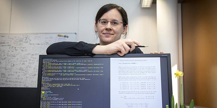 Eine Frau steht hinter einem Bildschirm. Sie hat die Hand auf den Bildschirm gelegt und hält einen Kugelschreiber. Auf dem Computerbildschirm ist bunte Schrift auf schwarzem Hintergrund und schwarze Schrift auf weißem Hintergrund zu sehen.
