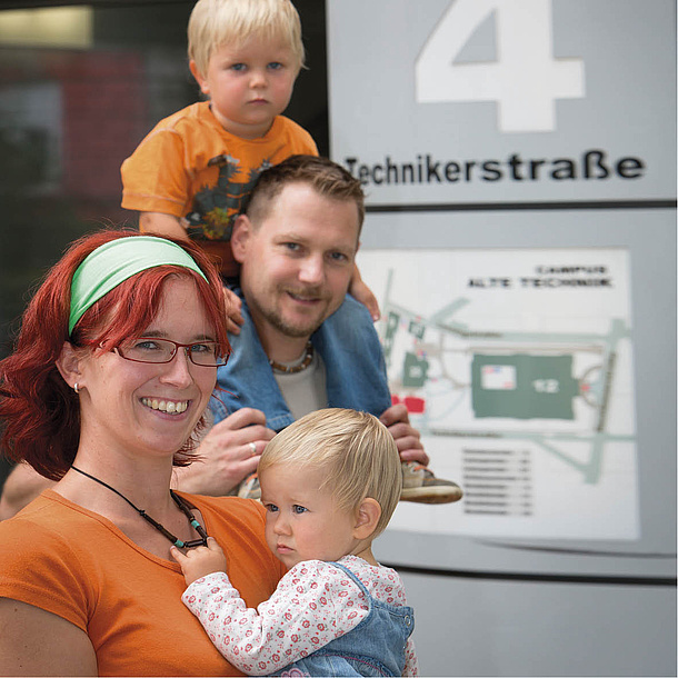 Couple with two children standing in front of an information board. Photo source: Lunghammer - TU Graz.