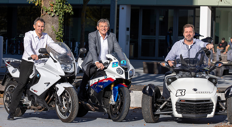 Three men with greying temples, in shirt and suit, cheerful, in a sunny spot, one of whom wears a grey jacket, on two BMW motorcycles and a quad motorbike with the inscription Rieberer.