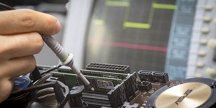 Eine Hand hält eine stiftförmiges Messgerät. Es ist auf das Innenleben eines Computers gerichtet.