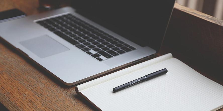 Laptop, Notizblock und Kugelschreiber auf einem Schreibtisch