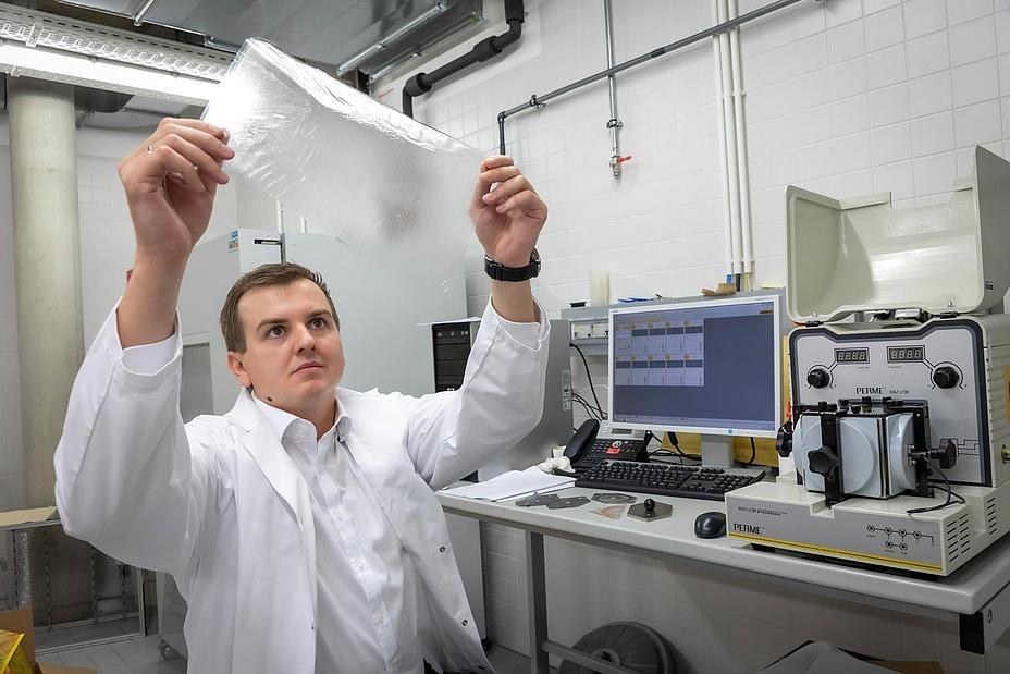 Forscher untersucht Kunststofffolie in Labor
