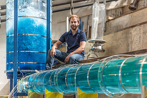 A young man with a beard in jeans and a blue T-shirt sits in the hydraulic engineering laboratory and is surrounded by experimental arrangements in the form of water-filled Plexiglas tubes.
