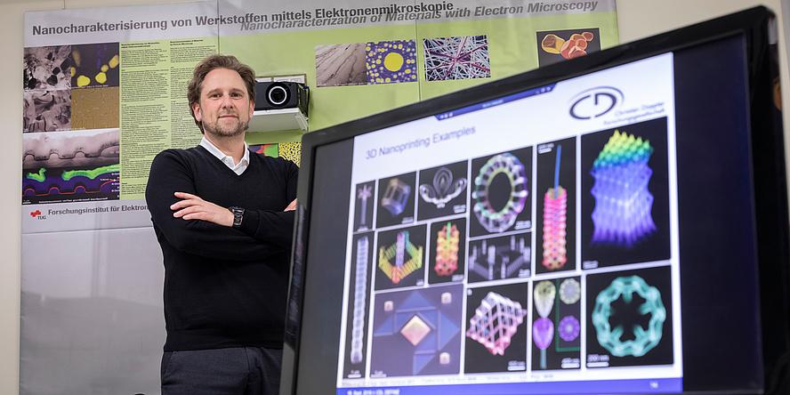 TU Graz researcher stands behind computer screen