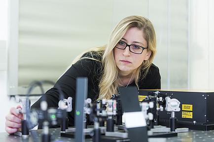 Frau mit Brille arbeitet an technischer Apparatur