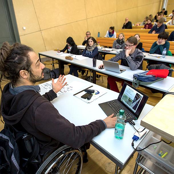 Mann im Rollstuhl in einem Hörsaal
