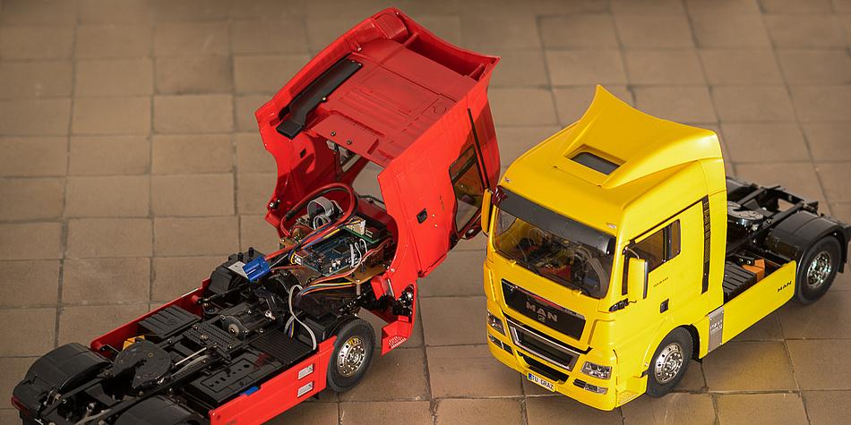 Ein roter und ein gelber Modell-LKW.