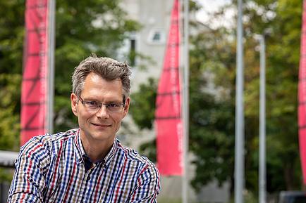 Porträt eines TU Graz-Forschers, im Hintergrund TU Graz Fahnen