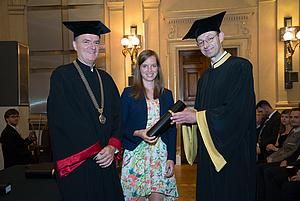 Dekan und Studiendekan überreichen das Zeugnis an die Absolventin in der Mitte
