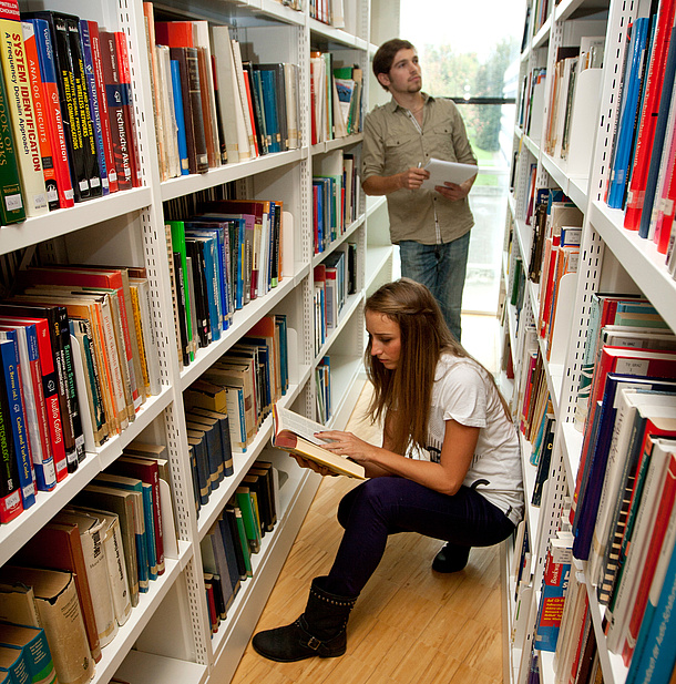 Two students in front of bookshelves.