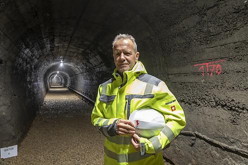 Mann mit Sicherheitsjacke und Helm unter dem Arm vor einem Tunnelportal.