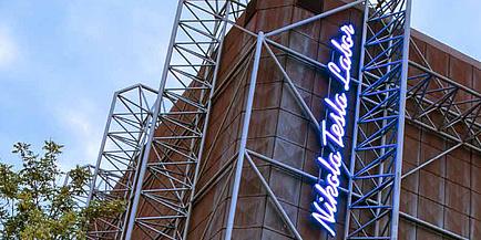 Ein futuristisches Gebäude, in beleuchteten Buchstaben, ist das Nikola Tesla Labor vertikal auf die Fassade geschrieben.