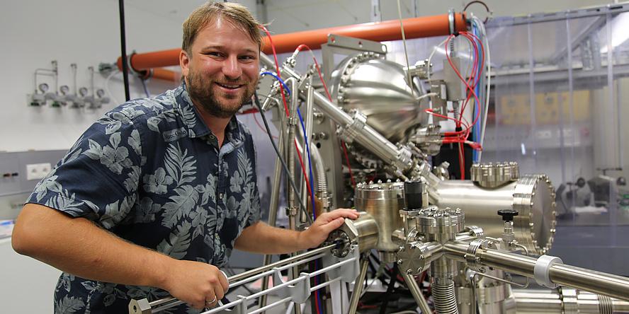Florian Lackner. Er trägt blonde kurze Haare und ein blaues Hemd mit Blumen. Er lächelt in die Kamera. Er steht neben einem Phototransmissionselektronenmikroskop.