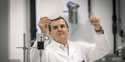 Samir Kopacic steht mit einem weißen Labormantel im Büro. In einer Hand hält er ein rundes, weißes Stück Papier, in der anderen ein Stück Plastikfolie.