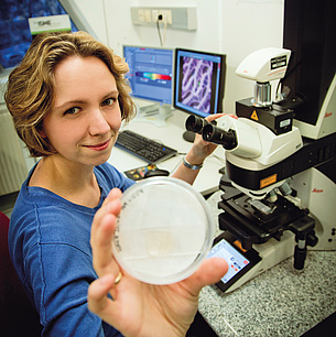 Young woman in front of a microscope presenting a petri dish. Photo source: Lunghammer - NAWI Graz