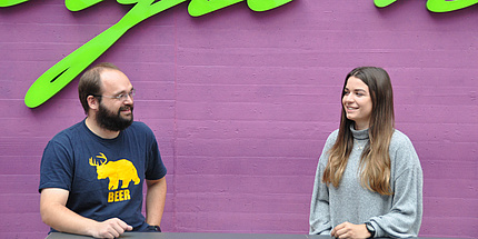 Mann mit Bart und junge Frau vor violetter Wand, an einem Tisch sitzend im Gespräch