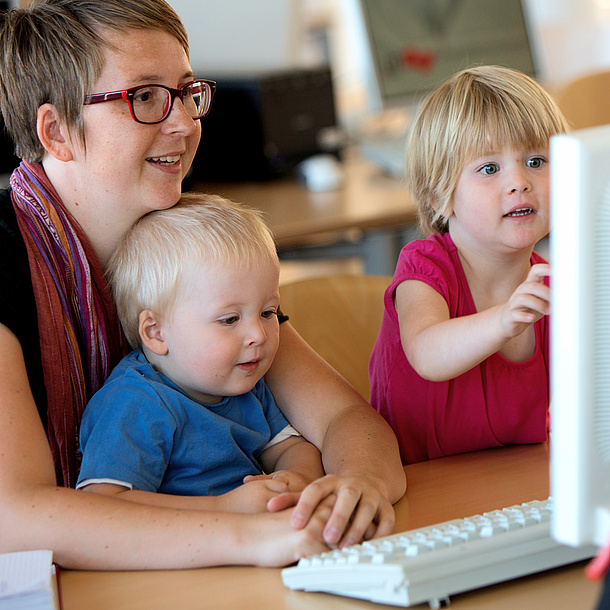 Mother with small kids in front of a PC. Photo source: Lunghammer - TU Graz