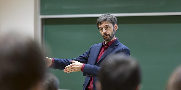 Ein Mann steht vor einer grünen Tafel und spricht zum Publikum.
